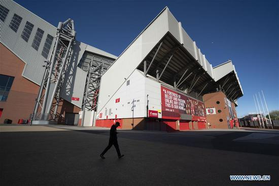 A man walks past Liverpool Football Club's Anfield Stadium as sport events continue to be suspended during the COVID-19 pandemic in Liverpool, Britain, May 2, 2020. (Photo by Jon Super/Xinhua)