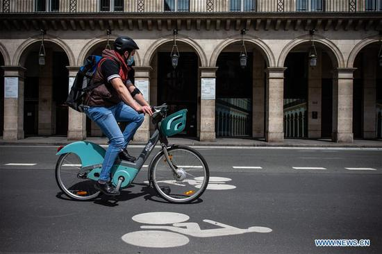 A man rides a bicycle on the famous Rue de Rivoli in Paris, France, May 8, 2020. France would start to ease restrictions on movement from next Monday through