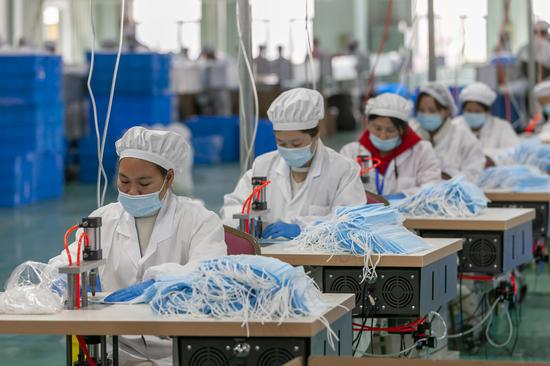 Workers make face masks at a factory in Shanghai, east China, April 8, 2020. (Photo by Wang Xiang/Xinhua)