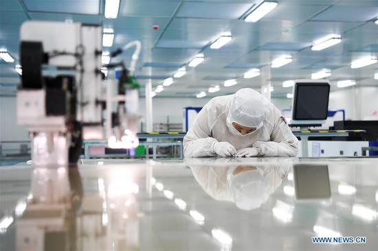 A worker assembles and tests a full-automatic picosecond laser cutting machine at Jiangsu Xianhe Laser Technology Co., Ltd. at Suqian Laser Industrial Park in Suqian City, east China's Jiangsu Province, May 14, 2020. There are over 50 laser-related companies so far in the park, among which some involves in laser cutting, laser marking and laser medical equipment. Local authorities have introduced measures to attract more laser industries to the park and support the building of a complete industry chain in laser's research and development, equipment manufacturing as well as processing and application. (Xinhua/Li Bo)