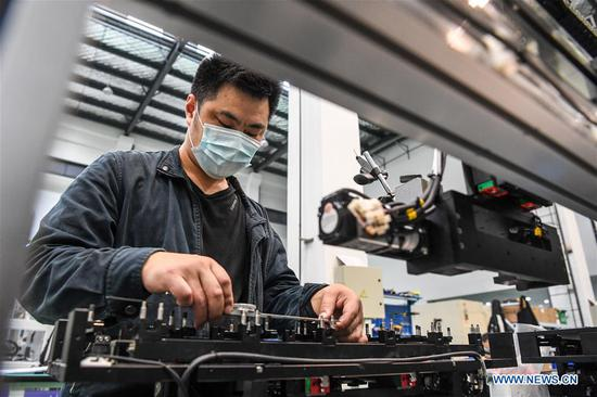 Workers work at an assembling workshop of Jiangsu Huake Chuangzhi Technology Co., Ltd. at Suqian Laser Industrial Park in Suqian City, east China's Jiangsu Province, May 13, 2020. There are over 50 laser-related companies so far in the park, among which some involves in laser cutting, laser marking and laser medical equipment. Local authorities have introduced measures to attract more laser industries to the park and support the building of a complete industry chain in laser's research and development, equipment manufacturing as well as processing and application. (Xinhua/Li Bo)