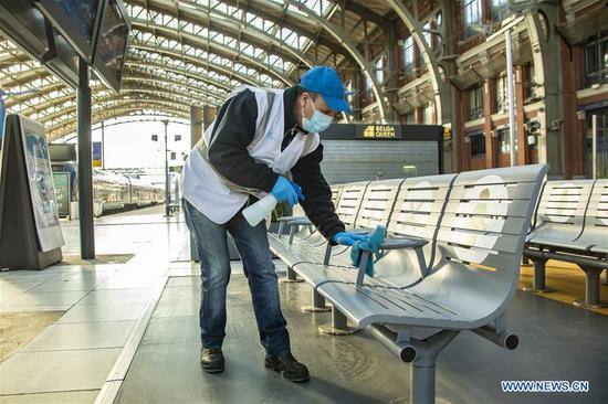 A staff member disinfects seats at the train station in Lille, northern France, May 14, 2020. From Monday, France started gradually lifting the two-month lockdown thanks to decelerating positive cases and the improved situation in hospitals. (Photo by Sebastien Courdji/Xinhua)
