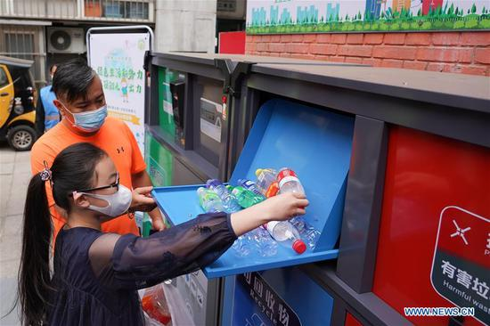 A child puts plastic bottles into the intelligent garbage bin of blue color at the Shaojiu residential community in Dongcheng District of Beijing, capital of China, May 17, 2020. The Shaojiu community on Sunday started a fine management project of household waste. Various measures including installing intelligent garbage bins and providing garbage bags imprinted traceable and different QR codes to households were taken to help residents better engage in garbage sorting. On May 1, Beijing started to carry out mandatory garbage sorting in new efforts to protect the environment. (Xinhua/Ju Huanzong)
