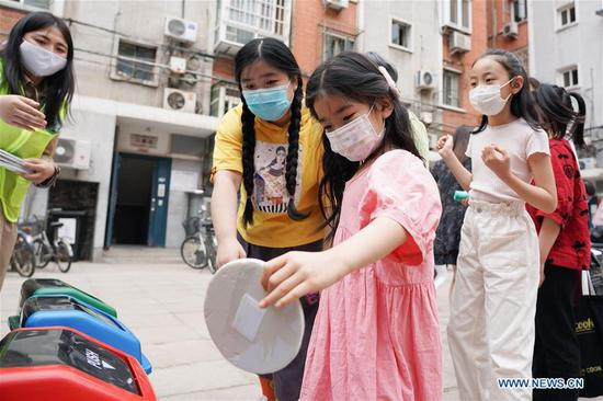 Children participate in a garbage sorting-themed game at the Shaojiu residential community in Dongcheng District of Beijing, capital of China, May 17, 2020. The Shaojiu community on Sunday started a fine management project of household waste. Various measures including installing intelligent garbage bins and providing garbage bags imprinted traceable and different QR codes to households were taken to help residents better engage in garbage sorting. On May 1, Beijing started to carry out mandatory garbage sorting in new efforts to protect the environment. (Xinhua/Ju Huanzong)