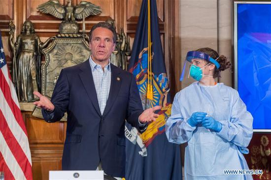 New York State Governor Andrew Cuomo (L) demonstrates how to get a COVID-19 test during a daily COVID-19 press briefing in Albany of New York State, the United States, on May 17, 2020. Cuomo announced on Sunday that New York State has doubled testing capacity to reach 40,000 tests per day, encouraging eligible New Yorkers to get tested for COVID-19. (Darren McGee/Office of Governor Andrew M. Cuomo/Handout via Xinhua)