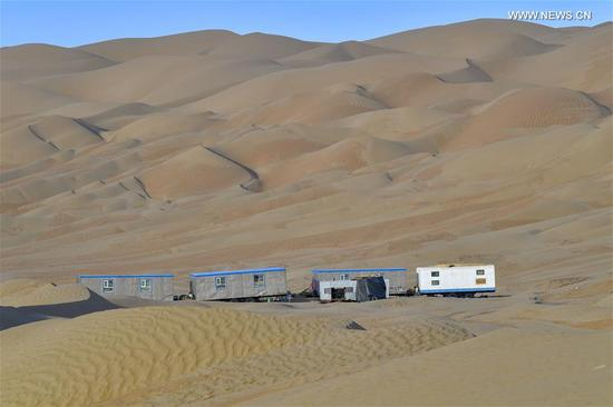 Photo taken on May 16, 2020 shows camps near the construction site of a highway in Taklimakan Desert, northwest China's Xinjiang Uygur Autonomous Region. The construction of Yuli-Qiemo highway, the third north-south route running through Taklimakan Desert, has entered the final rush. Workers of China Communications Construction Company Ltd. are working on the largest dune in this project, with an estimated volume of 1.2 million cubic meters of sand to deal with. They established camps next to the dune for the convenience of work, and receive daily necessities on a regular basis. The completion of the highway is expected to improve the transport conditions in southern Xinjiang and promote local development. (Xinhua/Hu Huhu)