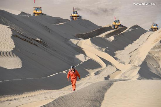 Worker Li Mingyou walks on a dune at the construction site of a highway in Taklimakan Desert, northwest China's Xinjiang Uygur Autonomous Region, May 16, 2020. The construction of Yuli-Qiemo highway, the third north-south route running through Taklimakan Desert, has entered the final rush. Workers of China Communications Construction Company Ltd. are working on the largest dune in this project, with an estimated volume of 1.2 million cubic meters of sand to deal with. They established camps next to the dune for the convenience of work, and receive daily necessities on a regular basis. The completion of the highway is expected to improve the transport conditions in southern Xinjiang and promote local development. (Xinhua/Song Yanhua)