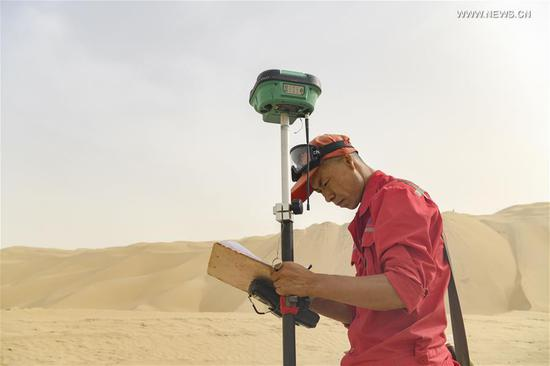 Surveyor Liu Yaojun works at the construction site of a highway in Taklimakan Desert, northwest China's Xinjiang Uygur Autonomous Region, May 17, 2020. The construction of Yuli-Qiemo highway, the third north-south route running through Taklimakan Desert, has entered the final rush. Workers of China Communications Construction Company Ltd. are working on the largest dune in this project, with an estimated volume of 1.2 million cubic meters of sand to deal with. They established camps next to the dune for the convenience of work, and receive daily necessities on a regular basis. The completion of the highway is expected to improve the transport conditions in southern Xinjiang and promote local development. (Xinhua/Hu Huhu)