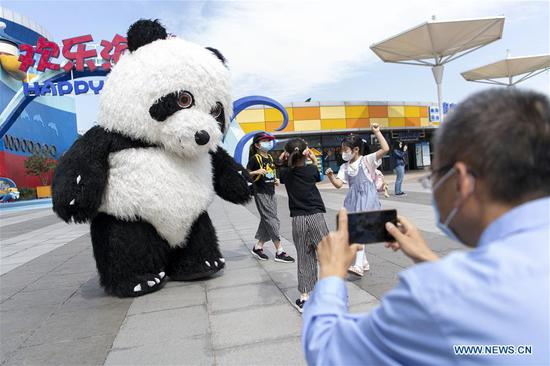 Tourists are entertained by a panda-costumed staff at the Happy Valley Wuhan theme park in Wuhan, central China's Hubei Province, May 19, 2020. Happy Valley Wuhan, a theme park which had been closed due to the COVID-19 outbreak, has partly reopened on Tuesday. Still, there is a limit on the number of visitors and online pre-booking is required. (Xinhua/Xiong Qi)