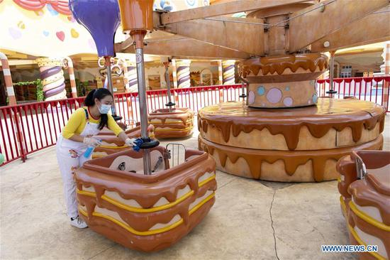 A staff disinfects an amusement ride at the Happy Valley Wuhan theme park in Wuhan, central China's Hubei Province, May 19, 2020. Happy Valley Wuhan, a theme park which had been closed due to the COVID-19 outbreak, has partly reopened on Tuesday. Still, there is a limit on the number of visitors and online pre-booking is required. (Xinhua/Xiong Qi)