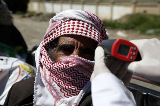 A health worker checks a traveler's temperature before he enters Sanaa as precautionary measures against the spread of COVID-19, in the southern entrance of Sanaa, Yemen, May 9, 2020. (Xinhua/Mohammed Mohammed)