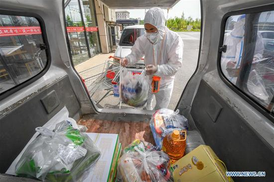 Staff member Li Yueguo loads the goods onto a truck at a supermarket in Shulan, northeast China's Jilin Province, May 20, 2020. Shulan, a county-level city in northeast China's Jilin Province, on Monday imposed complete closed-off management for local residential communities with confirmed or suspected COVID-19 cases. Local residential communities with confirmed or suspected cases are under complete close-off management, basically allowing no people to come in and go out without authorization. The stores and supermarkets are responsible for delivering daily necessities. (Xinhua/Zhang Nan)