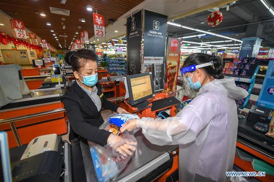 Staff member Xu Baoxia (L) prepares goods at a supermarket in Shulan, northeast China's Jilin Province, May 20, 2020. Shulan, a county-level city in northeast China's Jilin Province, on Monday imposed complete closed-off management for local residential communities with confirmed or suspected COVID-19 cases. Local residential communities with confirmed or suspected cases are under complete close-off management, basically allowing no people to come in and go out without authorization. The stores and supermarkets are responsible for delivering daily necessities. (Xinhua/Zhang Nan)