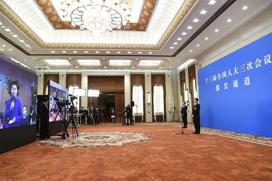 Chinese Minister of Commerce Zhong Shan gives an interview via video link after the second plenary meeting of the third session of the 13th National People's Congress (NPC) at the Great Hall of the People in Beijing, capital of China, May 25, 2020. (Xinhua/Jin Liangkuai)