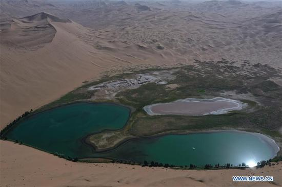 Aerial photo taken on May 30, 2020 shows a lake in Badain Jaran Desert, north China's Inner Mongolia Autonomous Region. There are many lakes in the Badain Jaran Desert, which constitute a beautiful picture with deserts and plants. (Xinhua/Xu Qin)