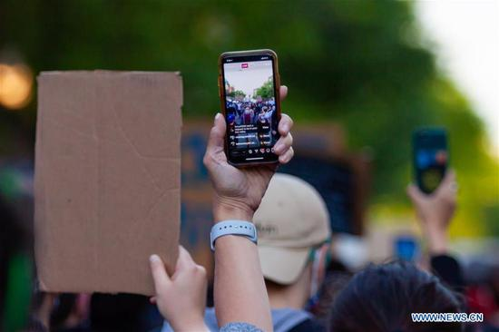 Demonstrators live-stream the protest via smartphones in Uptown neighborhood of Chicago, the United States, June 1, 2020. Two people were shot dead and at least 60 were arrested as protests and looting continued in Chicago neighborhoods and suburbs on Monday in response to the police killing of George Floyd. (Photo by Javage Logan/Xinhua)