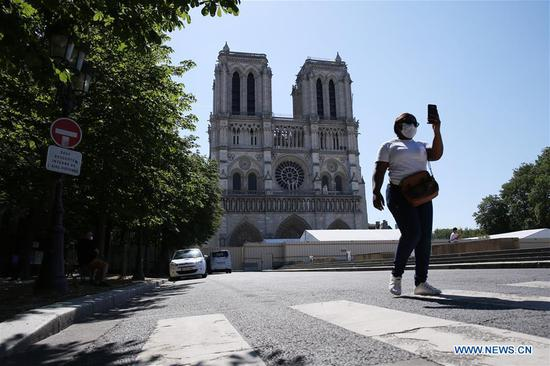 A woman walks in front of the Notre-Dame Cathedral in Paris, France, June 2, 2020. The Parvis Notre-Dame was reopened to the public from May 31 after more than one year's close because of the huge fire on April 15, 2019. (Xinhua/Gao Jing)