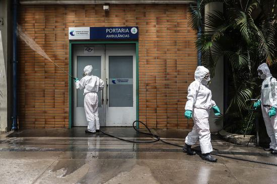 Staff members conduct disinfection at the Clinicas Hospital in Sao Paulo, Brazil, March 24, 2020. (Photo by Rahel Patrasso/Xinhua)