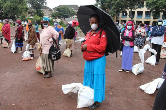 People keep social distancing after collecting food donations at a distribution center in Majengo slums, Nairobi, capital of Kenya, April 22, 2020. (Xinhua/Joy Nabukewa)