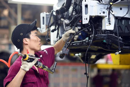 A man works on the production line at the passenger vehicle assembly plant of Anhui Jianghuai Automobile Group Corp., Ltd. in Hefei, east China's Anhui Province, June 19, 2020. (Xinhua/Zhou Mu)