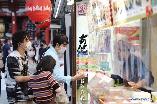 Visitors buy food at the sightseeing spot Asakusa, in Tokyo, Japan, June 21, 2020. Japan on Friday completely lifted its request for people not to travel across prefectural lines, with the move met by a return of passengers to airports and train stations. (Xinhua/Du Xiaoyi)