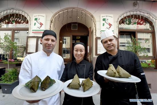 Wu bing (C), spaghetti chef Suman(R) and pizza chef Nuri show Zongzi at the restaurant Pizzeria Don Giovanni in Vienna, Austria, June 23, 2020. Zongzi is a traditional Chinese food made of glutinous rice wrapped in bamboo leaves for the occasion of Dragon Boat Festival. The restaurant Pizzeria Don Giovanni, operated by Wu Bing and her husband, serves Zongzi to locals in Vienna as the festival is upcoming. (Xinhua/Guo Chen)