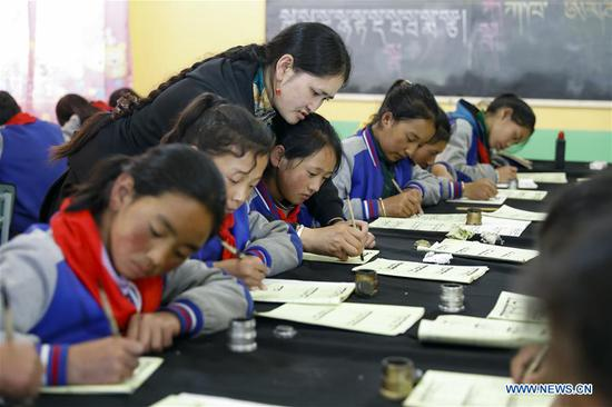 A teacher instructs as students learn Tibetan calligraphy in a primary school in Aba County of Aba Tibetan and Qiang Autonomous Prefecture, southwest China's Sichuan Province, June 14, 2020. Located in northwest of Sichuan Province, with nearly one million population, Aba Tibetan and Qiang Autonomous Prefecture has a diversity of ethnic minority groups, including Tibetan, Qiang and Hui, etc. In recent years, to better inherit the ethnic culture, local schools have introduced more traditional cultural courses while local authorities set up training workshops about intangible cultural heritage to help local villagers learn traditional crafts, as a way to boost their incomes. In 2018, the production value of cultural industry in this prefecture has reached about 1.2 billion yuan (about 169.8 million U.S. dollars), accounting for 3.32 percent of gross domestic product (GDP) of this prefecture. (Xinhua/Shen Bohan)