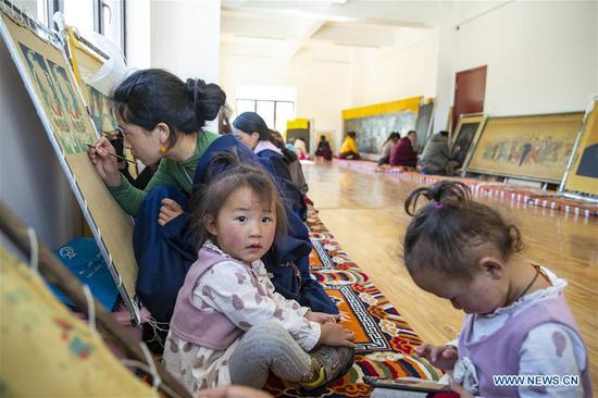 A villager accompanied by her twin daughters creates a Tangka painting at a workshop where villagers can learn traditional crafts for free in Rangtang County of Aba Tibetan and Qiang Autonomous Prefecture, southwest China's Sichuan Province, June 13, 2020. Located in northwest of Sichuan Province, with nearly one million population, Aba Tibetan and Qiang Autonomous Prefecture has a diversity of ethnic minority groups, including Tibetan, Qiang and Hui, etc. In recent years, to better inherit the ethnic culture, local schools have introduced more traditional cultural courses while local authorities set up training workshops about intangible cultural heritage to help local villagers learn traditional crafts, as a way to boost their incomes. In 2018, the production value of cultural industry in this prefecture has reached about 1.2 billion yuan (about 169.8 million U.S. dollars), accounting for 3.32 percent of gross domestic product (GDP) of this prefecture. (Xinhua/Shen Bohan)