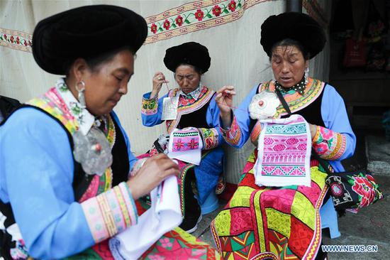 Villagers make embroidery of Qiang ethnic group in Maoxian County of Aba Tibetan and Qiang Autonomous Prefecture, southwest China's Sichuan Province, June 22, 2020. Located in northwest of Sichuan Province, with nearly one million population, Aba Tibetan and Qiang Autonomous Prefecture has a diversity of ethnic minority groups, including Tibetan, Qiang and Hui, etc. In recent years, to better inherit the ethnic culture, local schools have introduced more traditional cultural courses while local authorities set up training workshops about intangible cultural heritage to help local villagers learn traditional crafts, as a way to boost their incomes. In 2018, the production value of cultural industry in this prefecture has reached about 1.2 billion yuan (about 169.8 million U.S. dollars), accounting for 3.32 percent of gross domestic product (GDP) of this prefecture. (Xinhua/Shen Bohan)