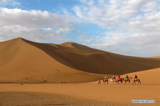 Tourists visit the Mingsha Mountain and Crescent Spring scenic area in Dunhuang, northwest China's Gansu Province, June 27, 2020. China saw around 48.81 million domestic tourist trips made during the Dragon Boat Festival holiday, bringing in 12.28 billion yuan (around 1.74 billion U.S. dollars), the Ministry of Culture and Tourism said Saturday. (Photo by Zhang Xiaoliang/Xinhua)
