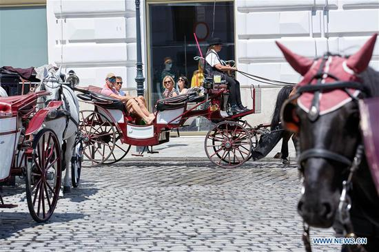 Tourists ride a horse-drawn carriage to visit the inner city of Vienna, Austria, on June 27, 2020. A number of European countries recently started exiting border controls cautiously at different paces while striving to reduce tourism fallout. (Photo by Georges Schneider/Xinhua)