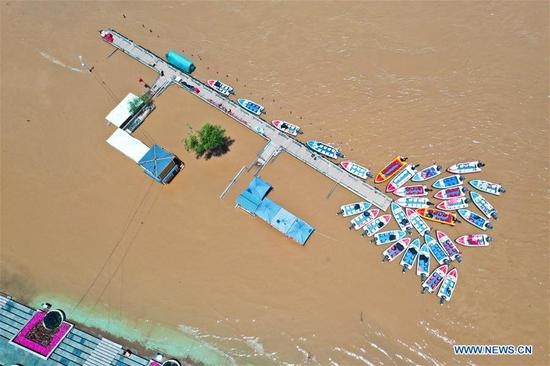 Aerial photo taken on June 27, 2020 shows a temporarily closed speedboat dock on the Yellow River in Lanzhou, northwest China's Gansu Province. Water level of the Lanzhou section of the Yellow River has risen due to continous rainfall and operations of reservoirs in the upper reaches. Some tourist attractions and facilities along the river have been temporarily closed. (Photo by Lang Bingbing/Xinhua)