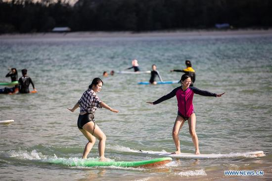 People learn surfing in the sea in Sanya, south China's Hainan Province, June 27, 2020. (Xinhua/Zhang Liyun)