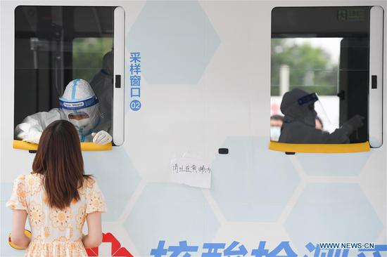 A medical staff member takes a throat swab sample from a woman at a newly-adopted mobile testing vehicle in Xicheng District of Beijing, capital of China, June 28, 2020. (Xinhua/Ju Huanzong)