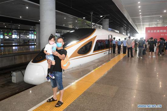 Passengers pose for a selfie with a bullet train, which heads for Hefei on the Shangqiu-Hefei-Hangzhou high-speed railway, before departure at Hangzhou East Railway Station in Hangzhou, east China's Zhejiang Province, June 28, 2020. A new high-speed railway route connecting east and central China started operation on Sunday. With a designed speed of 350 kph, the route connects the city of Shangqiu in central China's Henan Province, and Hefei and Hangzhou, the capital cities of east China's Anhui and Zhejiang provinces. (Xinhua/Huang Zongzhi)