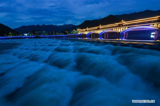 Photo taken on June 27, 2020 shows water flowing through a dam with scale-shaped geometric structures on the Huyuan River in Huyuan Township of Fuyang District, Hangzhou, east China's Zhejiang Province. Township-level governments in Fuyang District have worked in collaboration to maximize the Huyuan River's ecological resources and promote local ecotourism. (Xinhua/Xu Yu)