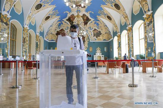 A voter wearing a face mask casts his ballot at a polling station in Moscow, Russia, on June 28, 2020. The all-Russian vote on constitutional amendments, postponed from April 22 due to the COVID-19 epidemic, began on June 25. Voting was originally scheduled to run for one day only on July 1, but election officials opened polls a week earlier to avoid overcrowding that could spread coronavirus infections. (Photo by Alexander Zemlianichenko Jr/Xinhua)
