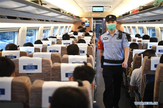 A railway police carries out inspection aboard a bullet train travelling from Hefei to Hangzhou on the Shangqiu-Hefei-Hangzhou high-speed railway on June 28, 2020. A new high-speed railway route connecting east and central China started operation on Sunday. With a designed speed of 350 kph, the route connects the city of Shangqiu in central China's Henan Province, and Hefei and Hangzhou, the capital cities of east China's Anhui and Zhejiang provinces. (Xinhua/Liu Junxi)