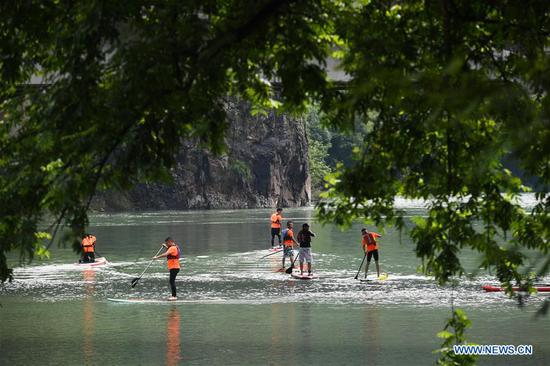 Water sports enthusiasts participate in a paddleboarding activity on the Huyuan River in Huyuan Township of Fuyang District, Hangzhou, east China's Zhejiang Province, June 28, 2020. Township-level governments in Fuyang District have worked in collaboration to maximize the Huyuan River's ecological resources and promote local ecotourism. (Xinhua/Xu Yu)