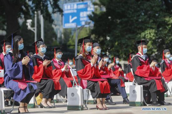Graduates attend the commencement ceremony of the Peking Union Medical College (PUMC) in Beijing, capital of China, June 30, 2020. Due to the coronavirus control measures, a few representatives attended the ceremony while the others participated via livestreaming. (Xinhua/Zhang Yuwei)