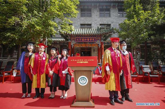 Graduates pose for photos with faculty members after the commencement ceremony of the Peking Union Medical College (PUMC) in Beijing, capital of China, June 30, 2020. Due to the coronavirus control measures, a few representatives attended the ceremony while the others participated via livestreaming. (Xinhua/Zhang Yuwei)