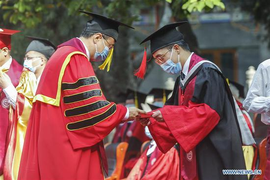 A graduate participates in the commencement ceremony of the Peking Union Medical College (PUMC) in Beijing, capital of China, June 30, 2020. Due to the coronavirus control measures, a few representatives attended the ceremony while the others participated via livestreaming. (Xinhua/Zhang Yuwei)