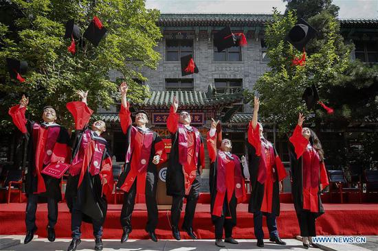 Graduates celebrate their graduation after the commencement ceremony of the Peking Union Medical College (PUMC) in Beijing, capital of China, June 30, 2020. Due to the coronavirus control measures, a few representatives attended the ceremony while the others participated via livestreaming. (Xinhua/Zhang Yuwei)