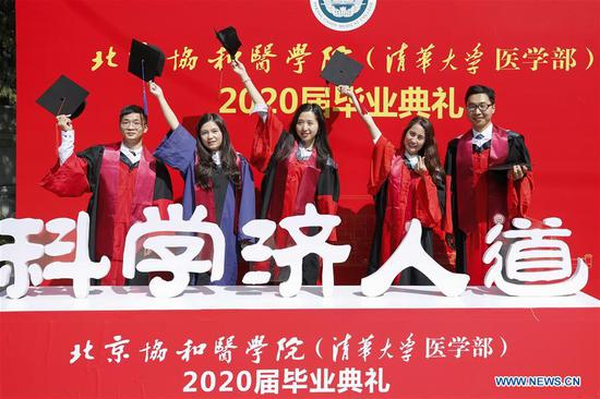 Graduates pose for photos after the commencement ceremony of the Peking Union Medical College (PUMC) in Beijing, capital of China, June 30, 2020. Due to the coronavirus control measures, a few representatives attended the ceremony while the others participated via livestreaming. (Xinhua/Zhang Yuwei)