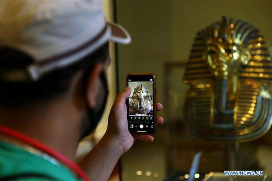 A man takes photos of the golden mask of King Tutankhamun at Egyptian Museum in Cairo, Egypt, on July 1, 2020. Egypt reopened on Wednesday the Egyptian Museum, the Giza Pyramids, and Temple of Luxor for the first time since the COVID-19 closure in March. (Xinhua/Ahmed Gomaa)
