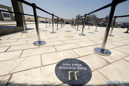 A sign reminding people of keeping a distance is seen near the ticket office of the Giza Pyramids in Giza, Egypt, on July 1, 2020. Egypt reopened on Wednesday the Egyptian Museum, the Giza Pyramids, and Temple of Luxor for the first time since the COVID-19 closure in March. (Xinhua/Ahmed Gomaa)