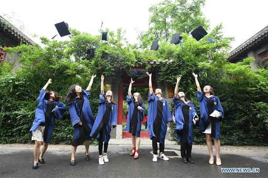 Graduates throw their hats in the air at Peking University in Beijing, capital of China, July 2, 2020. Peking University held its commencement ceremony in Beijing on Thursday. Due to COVID-19 prevention and control measures, a limited number of graduates attended the ceremony at nine venues on site while others participated online. (Xinhua/Ren Chao)