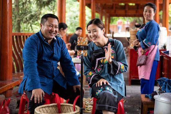 Ma Huihuang (L), leader of the poverty relief team of Shibadong Village, together with villager Shi Linjiao, promotes local products via live streaming at Shibadong Village of Xiangxi Tujia and Miao Autonomous Prefecture, central China's Hunan Province, May 15, 2020. (Xinhua/Chen Sihan)