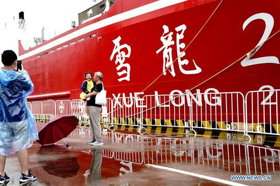 People pose for photos against the background of Xuelong 2, or Snow Dragon 2, China's first domestically built polar icebreaker, which moors at a port in Shanghai for a Maritime Day theme activity on July 11, 2020. July 11 marks the Maritime Day of China. (Xinhua/Zhang Jiansong)