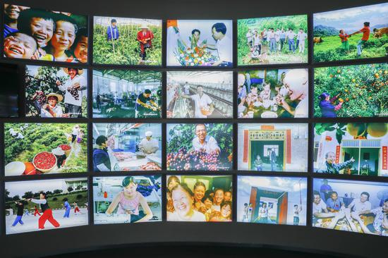 Photo taken on June 22, 2020 shows a photo wall displaying the happy life of people who have settled down after their relocation from the Three Gorges Reservoir area at the Three Gorges Migration Memorial in Wanzhou District, southwest China's Chongqing Municipality. (Xinhua/Huang Wei)